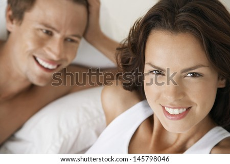 Closeup portrait of beautiful young woman with man in bed