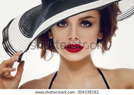 Closeup portrait of beautiful young woman with red lips wearing big striped summer hat. Studio shot over white background. - stock photo