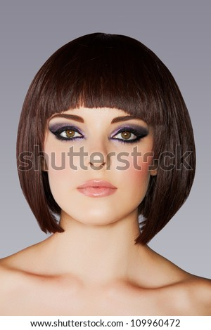 closeup portrait of beautiful young woman with short brown hair and dramatic eye makeup of purple eyeshadow and eyeliner . - stock photo