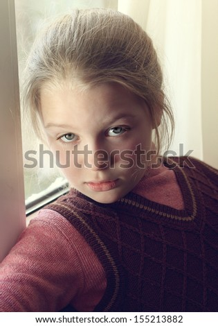 Closeup portrait of beautifull little girl near a window - stock photo