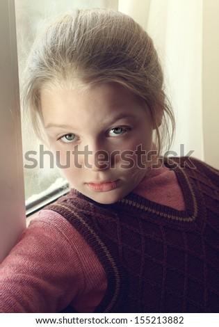 Closeup portrait of beautifull little girl near a window - stock photo