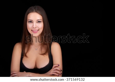 Closeup portrait of beauty woman smiling in black bra showing her ample cleavage, over black background - stock photo