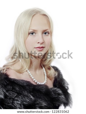 Closeup portrait of blonde woman with pearls in fur on white - stock photo
