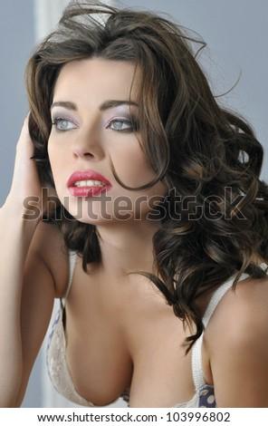 Closeup portrait of brunette female model with blue eyes on light blue background - stock photo