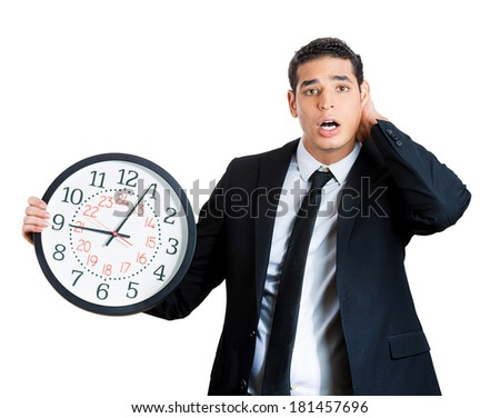 Closeup portrait of business man, funny worker holding clock stressed, running out pressured by lack of time, trying to stop, hold it, late for meeting, isolated on white background. Negative emotion