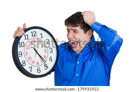 Closeup portrait of business man, student, worker, guy holding clock looking anxiously, pressured by lack, running out of time, isolated on white background. Human face expressions, emotions, reaction - stock photo