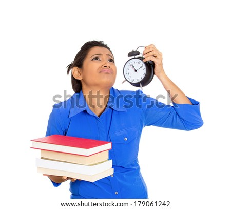 Closeup portrait of busy nervous young woman carrying tons of books and clock, stressed from project deadline, isolated on white background. Negative emotion facial expression feelings, body language - stock photo