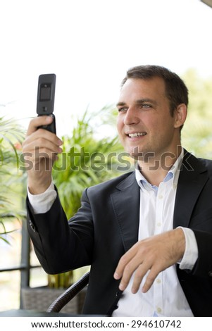 Closeup portrait of casual businessman talking on mobile phone in summer street