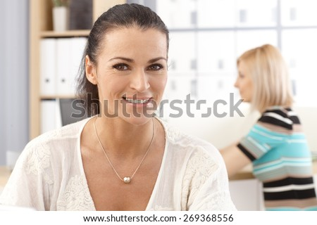 Closeup portrait of casual, happy, smiling, brunette, caucasian secretary at business office. - stock photo