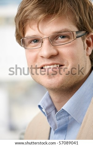 Closeup portrait of casual young businessman with glasses, smiling.?