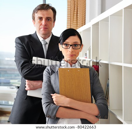 Closeup portrait of caucasian colleagues: young woman holding folder with documents and mature man holding laptop at the back - stock photo