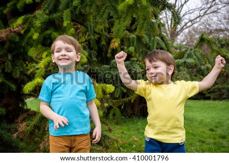 Closeup portrait of Caucasian two little brothers boys laughing outside in park on summer day, backlit with sun from behind, rim light of his figure, selective focus, shallow depth of field Jumping