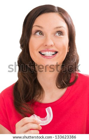 Closeup portrait of charming woman wearing orthodontic braces holding silicone trainer and smiling - stock photo