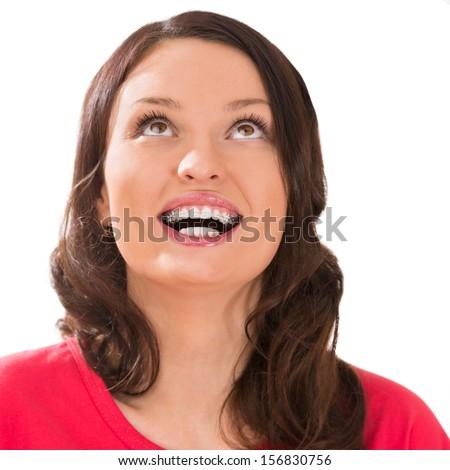 Closeup portrait of charming woman wearing orthodontic braces looking upwards - stock photo