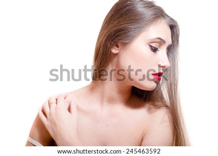 closeup portrait of charming woman with red lips looking down touching her naked shoulder - stock photo