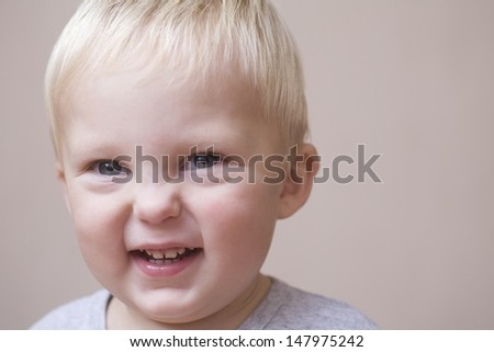 Closeup portrait of cheerful baby boy on colored background