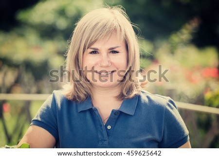 closeup portrait of cheerful smiling blond mature woman enjoying her time in garden on summer day - stock photo