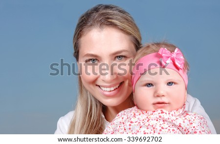 Closeup portrait of cheerful smiling mother with nice baby girl on hands isolated on blue background, happy family life