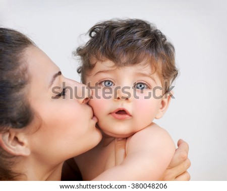 Closeup portrait of cheerful young mother kissing in cheek her precious little son, isolated on gray background, happy family life - stock photo