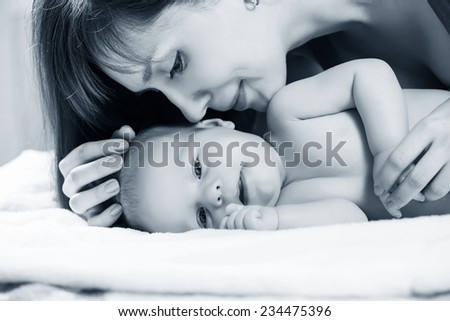 Closeup portrait of cheerful young mother with adorable newborn baby having fun at home, child care, happy parenthood, love concept - stock photo