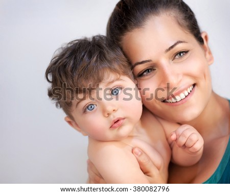 Closeup portrait of cheerful young mother with cute little baby boy isolated on gray background, happy family together