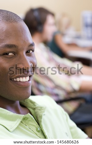 Closeup portrait of confident African American businessman with colleagues in background - stock photo