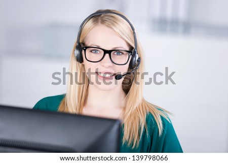 Closeup portrait of confident female customer service executive speaking on headset in office - stock photo