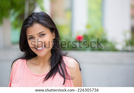 Closeup portrait of confident smiling happy pretty young woman in pink dress, isolated background of blurred trees, flowers. Positive human emotion facial expression feelings, attitude, perception - stock photo