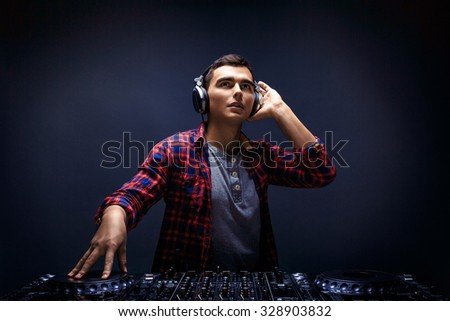 Closeup portrait of confident young DJ with stylish haircut and headphones on head mixing music on mixer looking up while standing isolated on dark background - stock photo