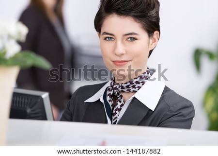 Closeup portrait of confident young receptionist at reception - stock photo