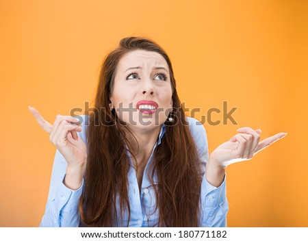 Closeup portrait of confused young woman pointing in two different directions, not sure which way to go in life, isolated on orange background. Negative emotion facial expression feeling body language - stock photo