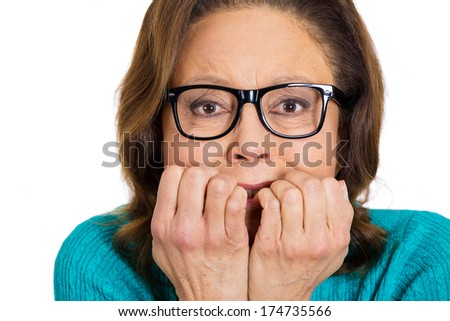 Closeup portrait of coy senior mature nerdy woman wearing glasses biting fingernails in stress craving something scared, isolated on white background. Negative emotion facial expression feelings. - stock photo