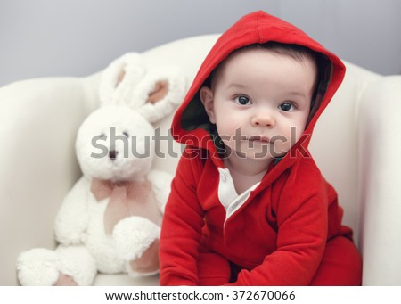Closeup portrait of cute adorable Caucasian baby boy girl with black brown eyes in red hoodie shirt sitting in chair with toy looking directly in camera - stock photo