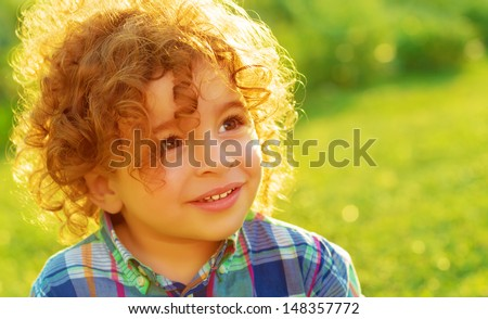 Closeup portrait of cute baby boy with curly hair on green field, having fun outdoors, enjoying summer vacation, happy childhood concept - stock photo