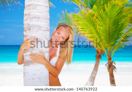Closeup portrait of cute blond female hugging palm tree trunk, luxury tropical resort, summer vacation, relaxation on the beach - stock photo