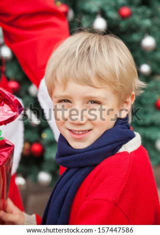 Closeup portrait of cute boy receiving gift from Santa Claus outdoors - stock photo