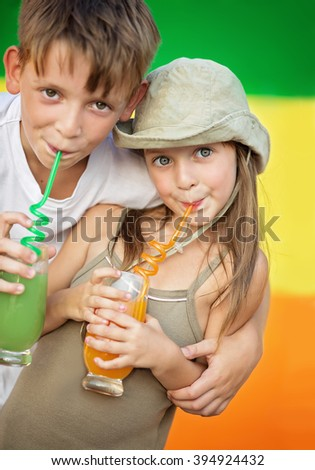 Closeup portrait of cute children drinking orange juice in the summer outdoors - stock photo