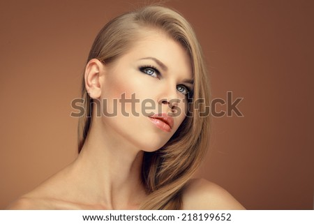 Closeup portrait of cute fashionable blonde with beautiful hairstyle posing in studio. Young attractive Caucasian female with healthy glossy hair.  - stock photo