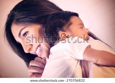 Closeup portrait of cute little baby sleeping on mothers shoulder, happy young loving family, new life concept - stock photo