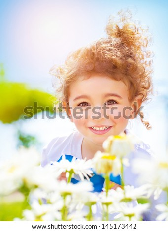 Closeup portrait of cute little boy having fun on daisy field, sweet child relaxing outdoors, happy summer holidays, joy and pleasure concept - stock photo