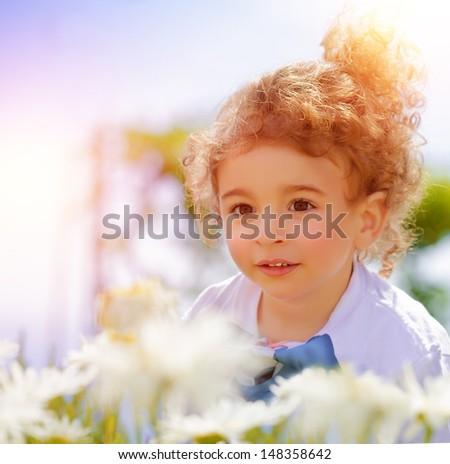 Closeup portrait of cute little boy on daisy field, having fun in beautiful park, summer holidays, recreation outdoors, carefree childhood - stock photo