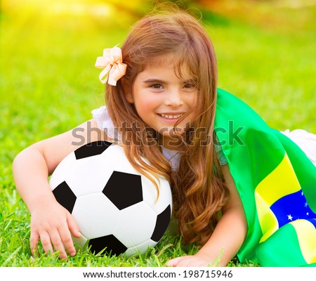 Closeup portrait of cute little football fan lying down on fresh green grass with ball and big Brazil flag, happy supporter of Brazilian football team - stock photo