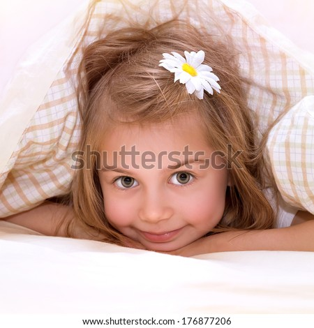 Closeup portrait of cute little girl with flower in hair lying down in the bed, covered with soft blanket, nap in daycare, comfort and happiness concept - stock photo