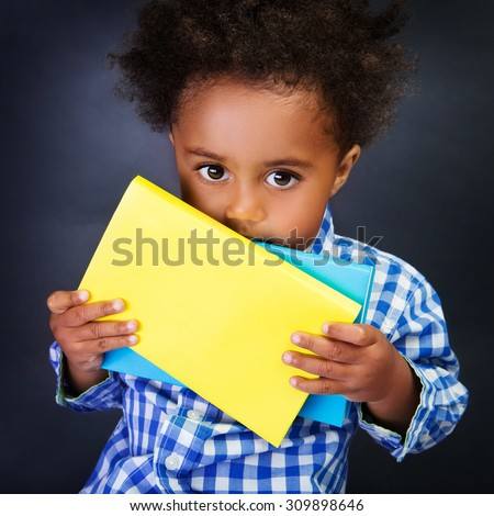 Closeup portrait of cute little shy American schoolboy with textbooks in hands over blackboard background, ready to study in elementary school - stock photo