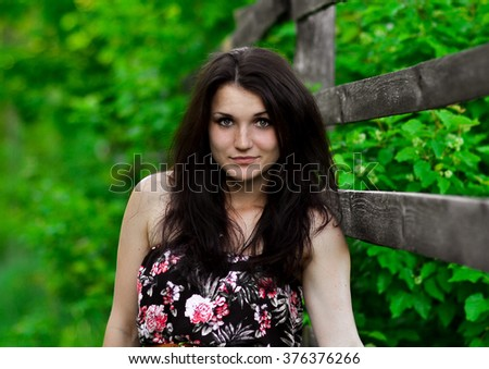 Closeup portrait of cute,lovely,nice,cheerful,smiling,attractive,beautiful girl,model near the wooden fence in greenery,green garden,park,forest.Beautiful girl in green forest in summer,summertime. - stock photo