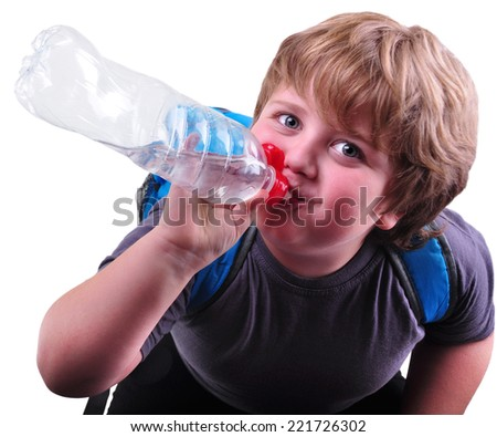 Closeup portrait of cute schoolboy drinking water. Isolated over white background - stock photo