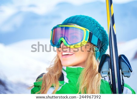 Closeup portrait of cute smiling skier girl wearing sportive mask and holding in hands ski, active winter vacation, happiness and enjoyment concept - stock photo