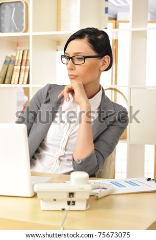 Closeup portrait of cute young business woman smiling at her workplace in an office environment - stock photo