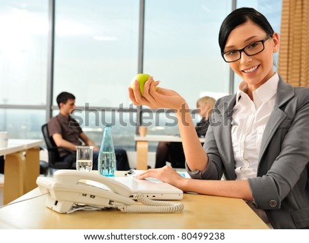 Closeup portrait of cute young business woman smiling at her workplace in an office environment. She is resting and eating green apple. Looking at the camera