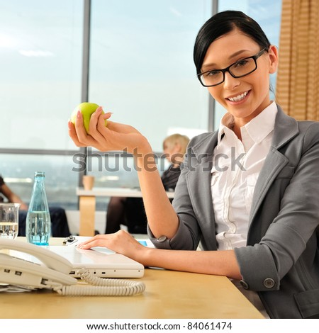 Closeup portrait of cute young business woman smiling at her workplace in an office environment. She is resting and eating green apple. Looking at the camera - stock photo